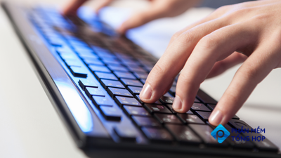 A person's hands typing on a keyboard with blue backlighting