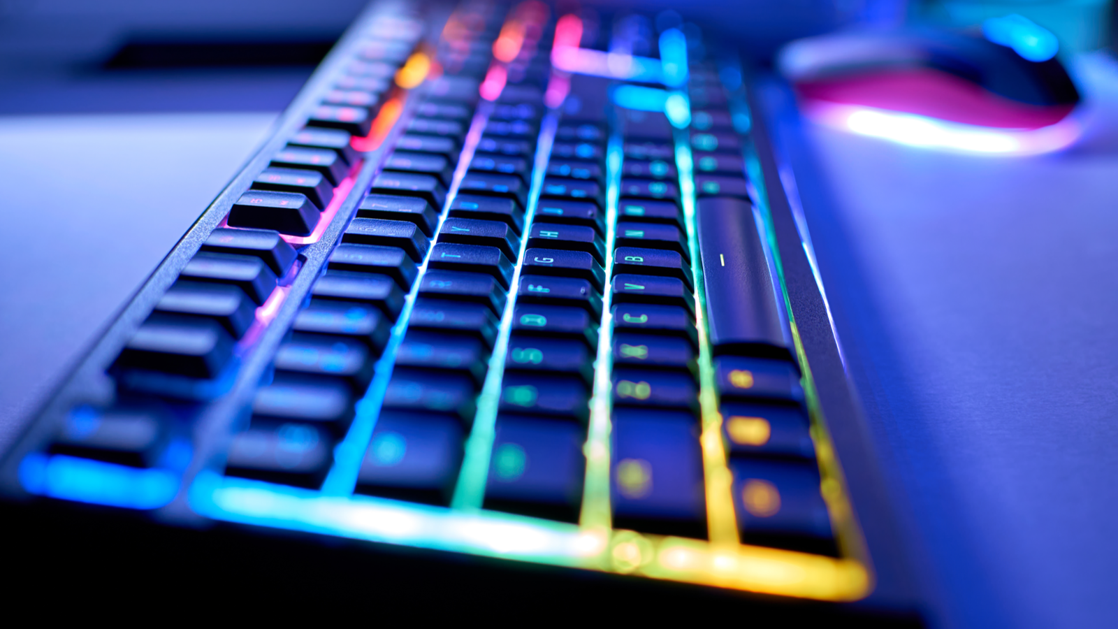 Gaming keyboard with RGB LED light, blurred background, selective focus, bokeh