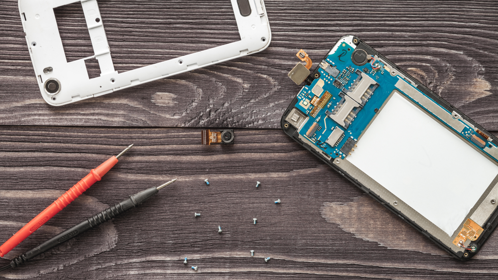Mobile phone repair, shot of interior of phone next to exterior case on wooden planks