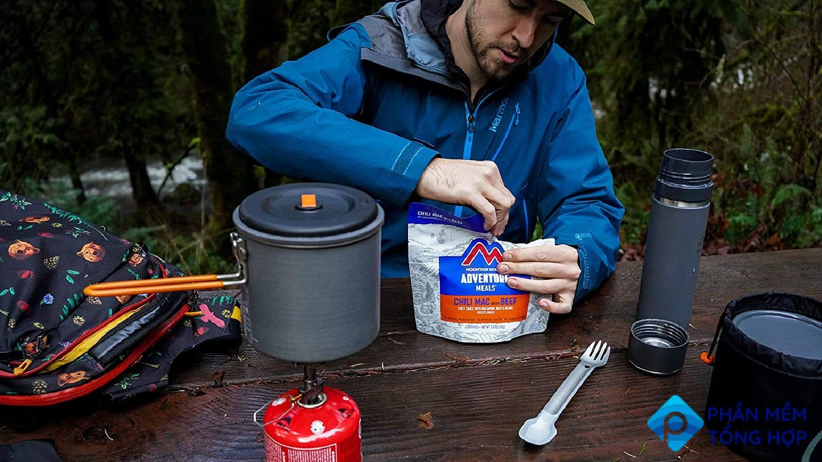 A camper opening up his Mountain House Meal before enjoying a hot dinner on a camping trip.