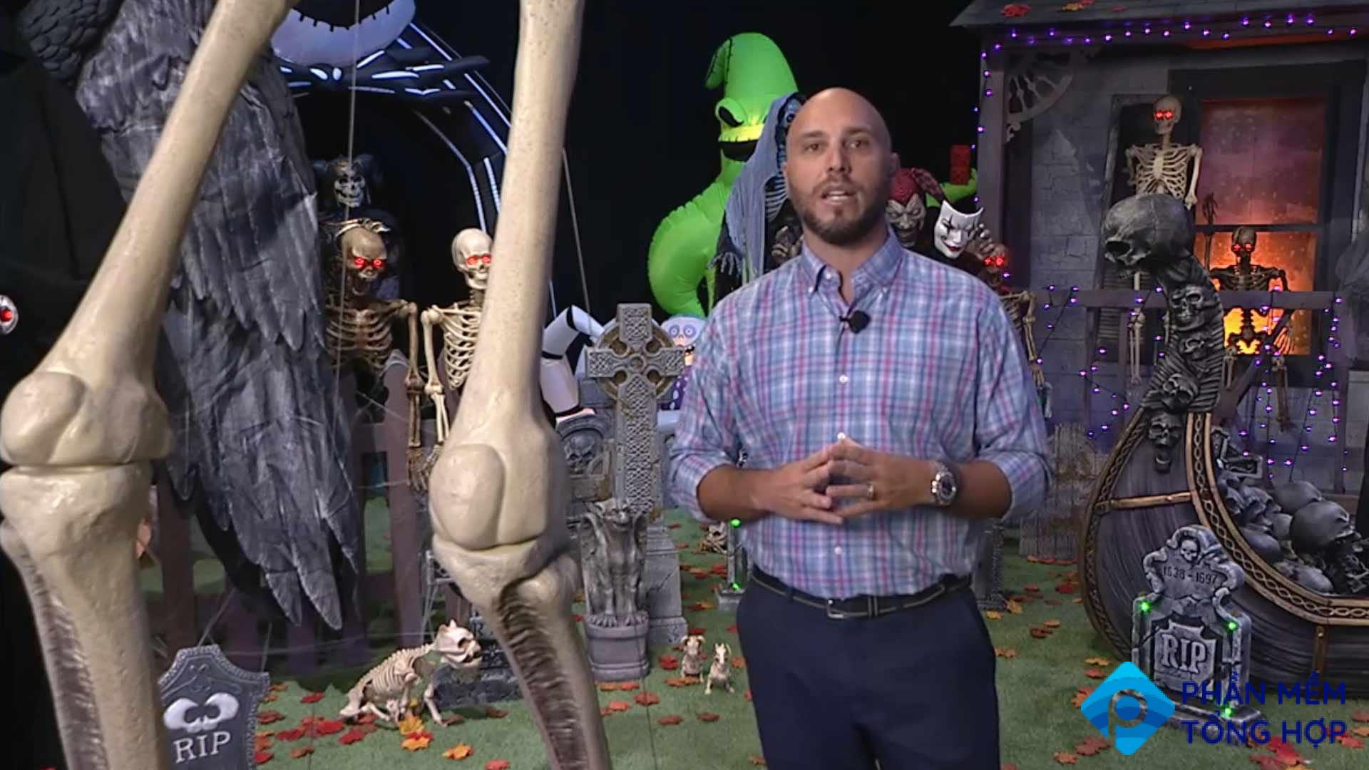A man standing next to a giant prop skeleton.