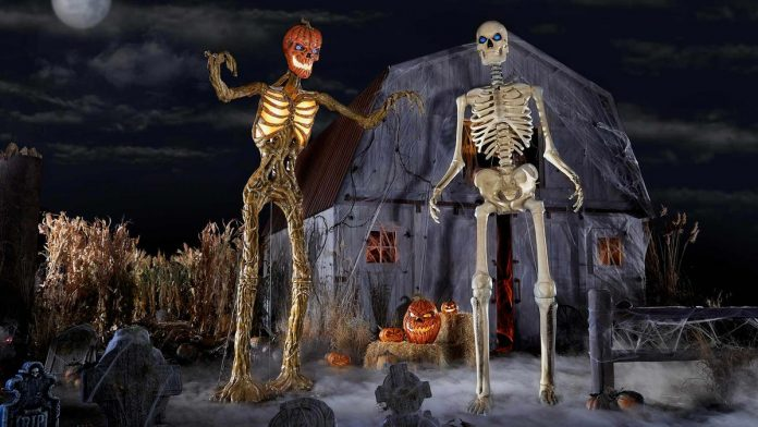 Two Halloween prop skeletons standing in front of a barn.
