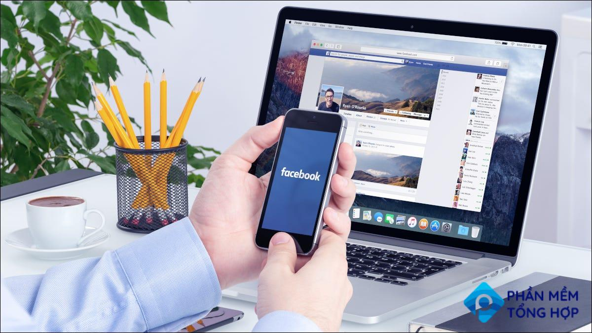 Hands holding a smartphone in front of laptop with Facebook open