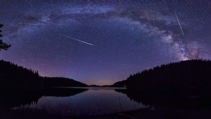 A meteor shower over a lake.