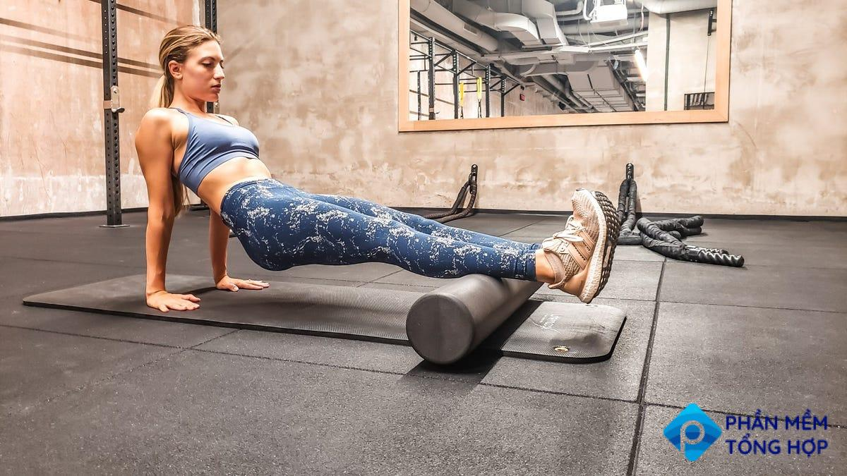 Woman foam rolling the calves in the gym