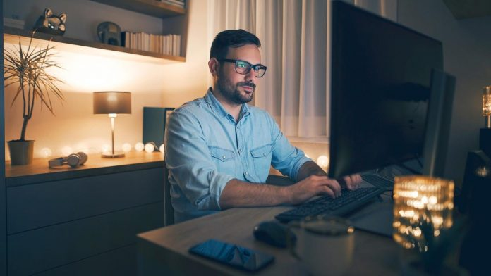 A man working at his computer in the evening, highly focused on a project.