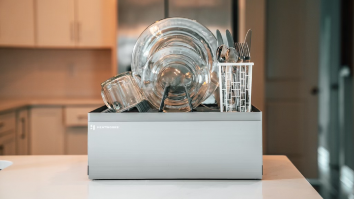 The Heatworks Tetra dishwasher sits on a countertop with multiple sets of dish-ware inside.