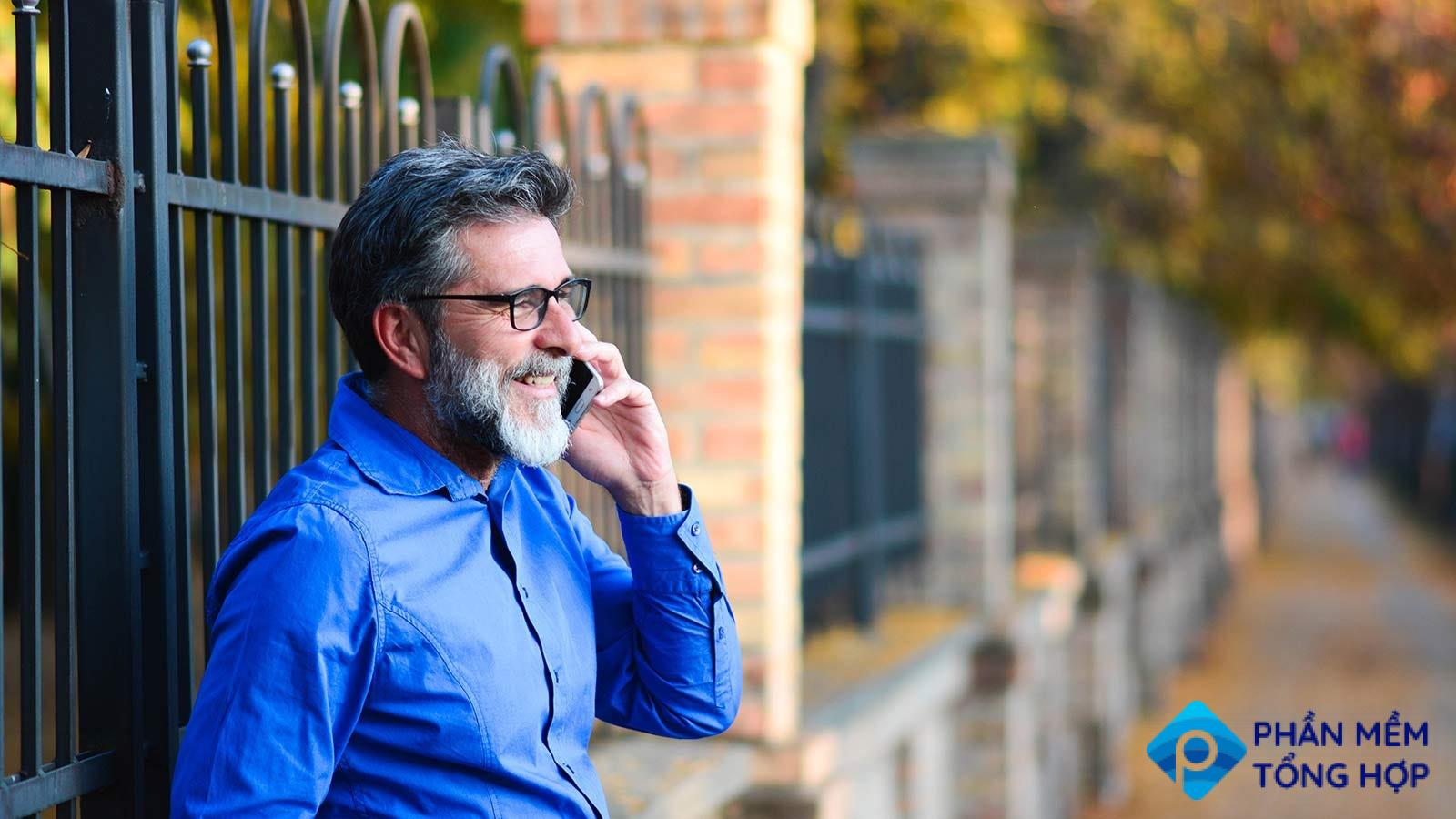 A man leaning against an iron fence, while talking on the phone.