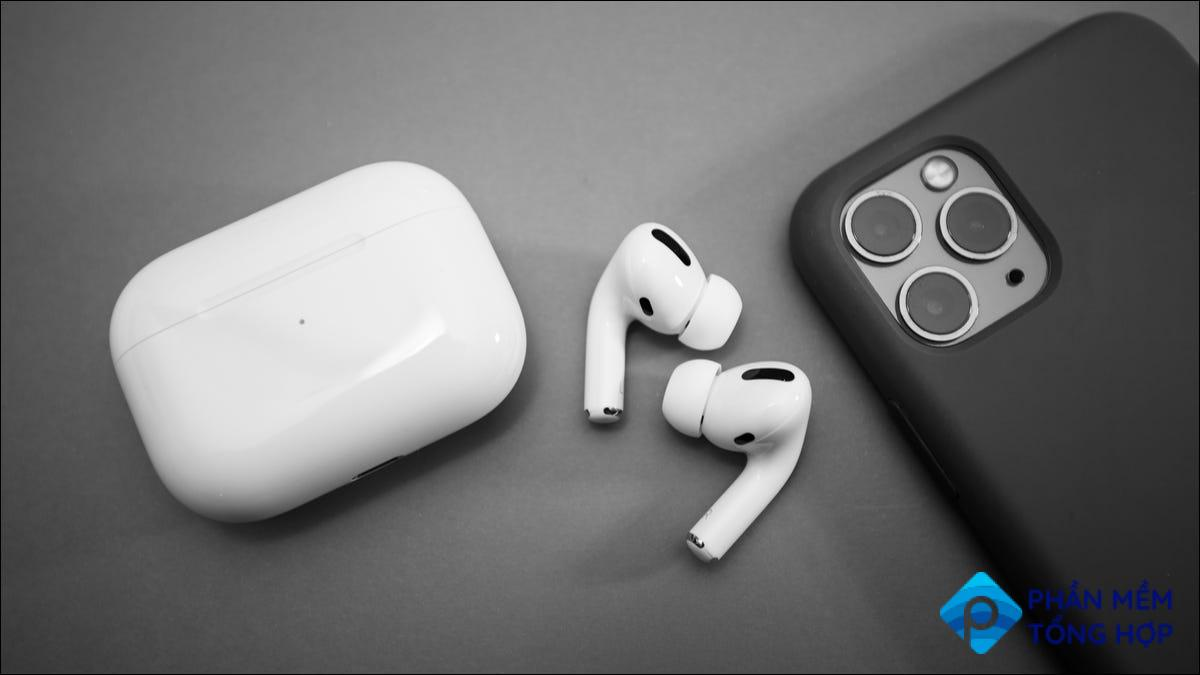 airpods pro on grey table next to iPhone