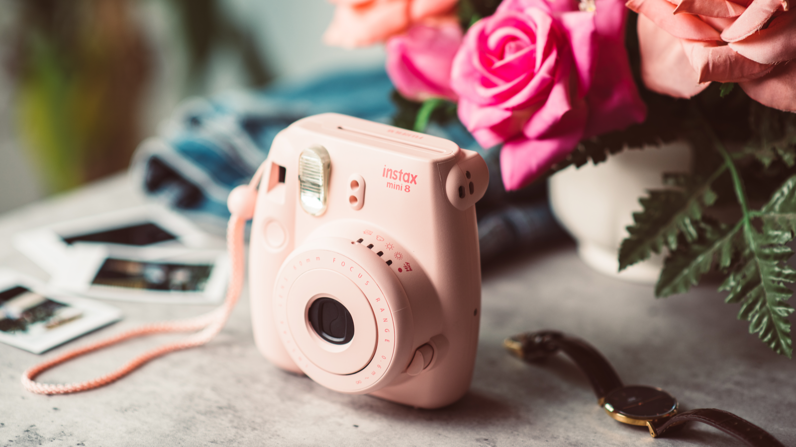 The pink Fujifilm Instax mini 8 on table next to photos, a watch, and a small vase of bright roses
