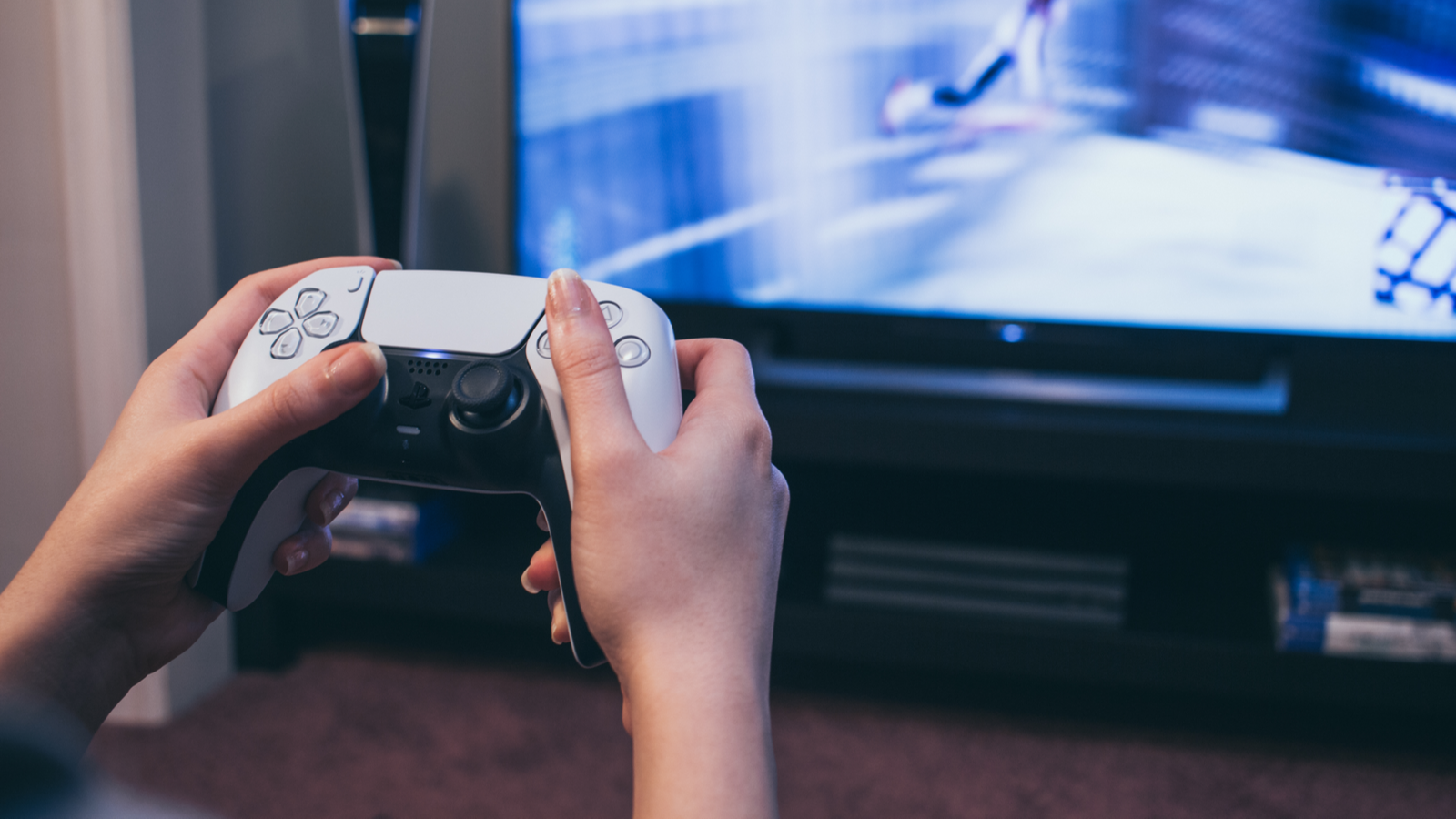 Person holding the PlayStation 5 DualSense controller playing a game on a large TV