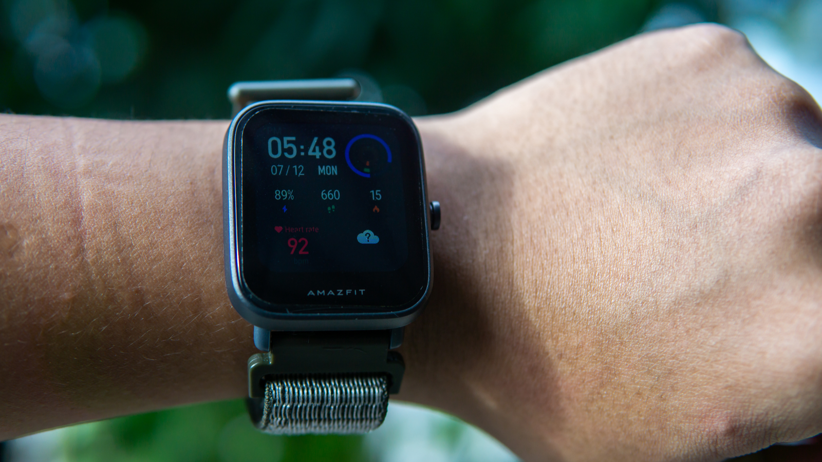 Amazfit smartwatch fitness tracker on wrist showing time and other metrics