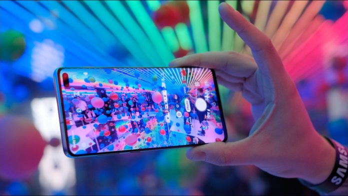 Hand holding a Samsung Galaxy S10 with a coloful display in front of multicolored lights.