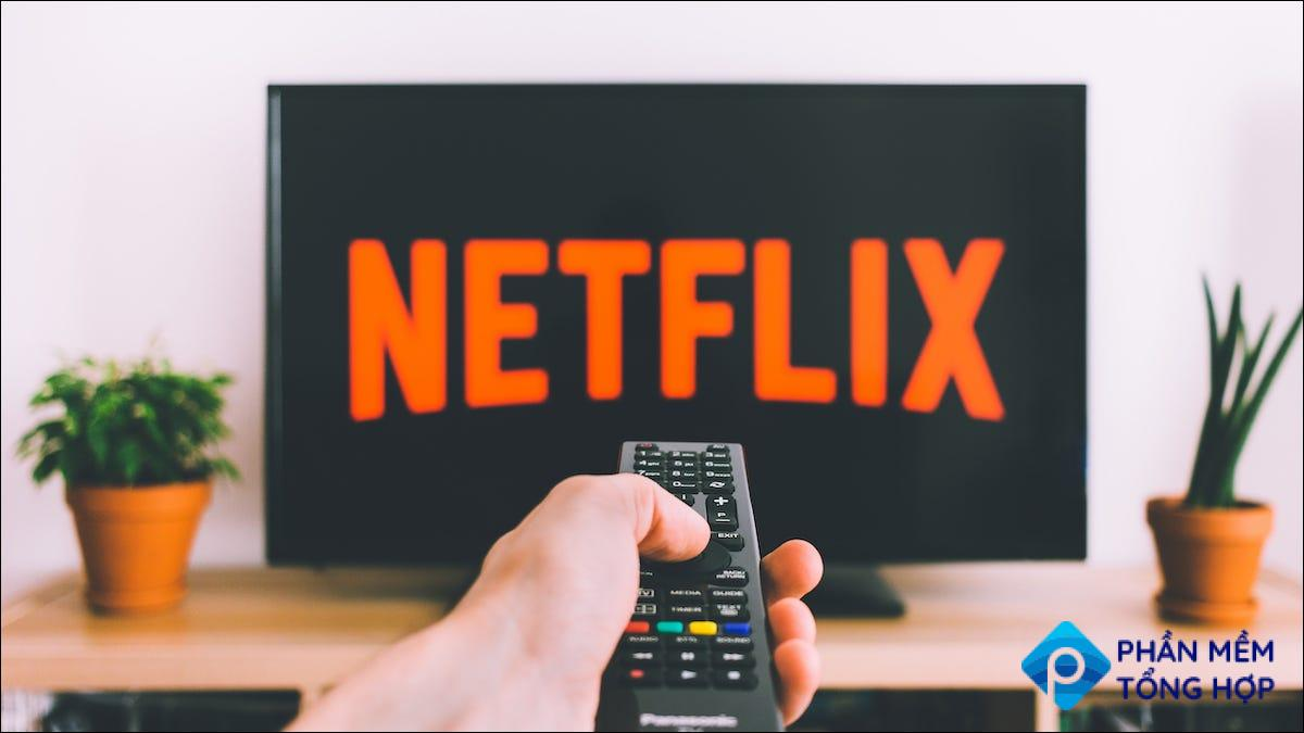 Person pointing a remote towards a TV with the Netflix logo