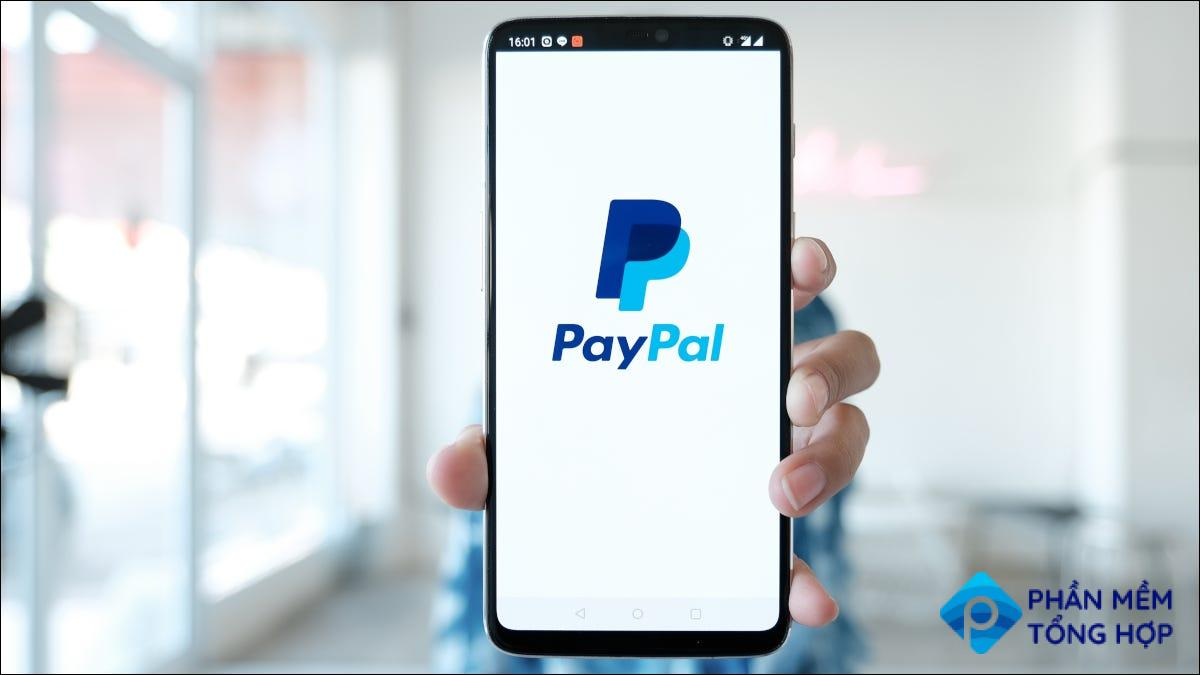 Hand holding smartphone with PayPal logo displaying