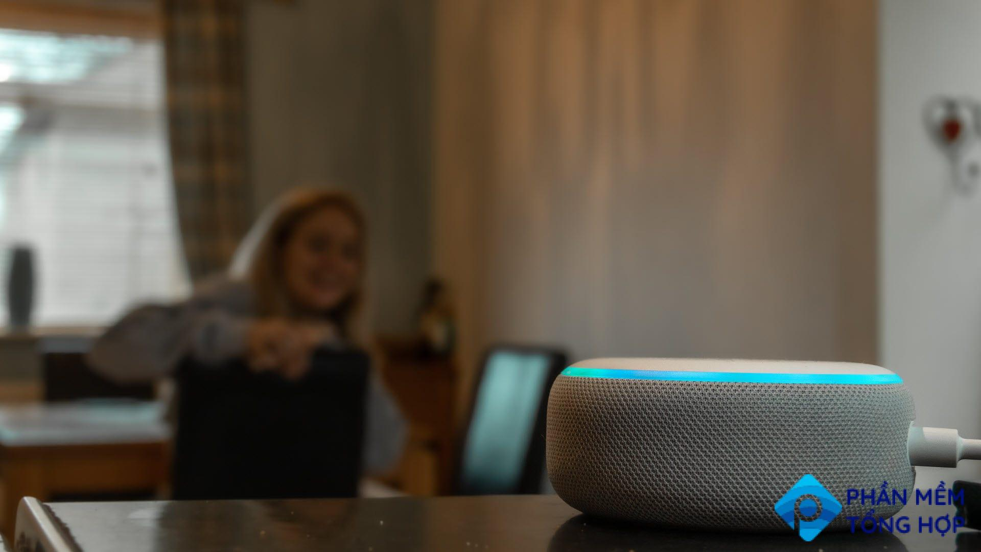 A woman talking to an Amazon Echo dot while frowning.