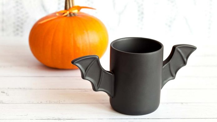 A bat-wing mug sitting on a table in front of a pumpkin.