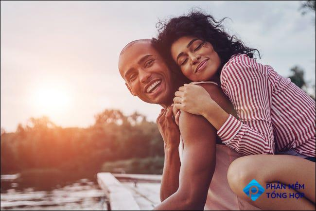 A couple embracing and looking happy on a lake dock