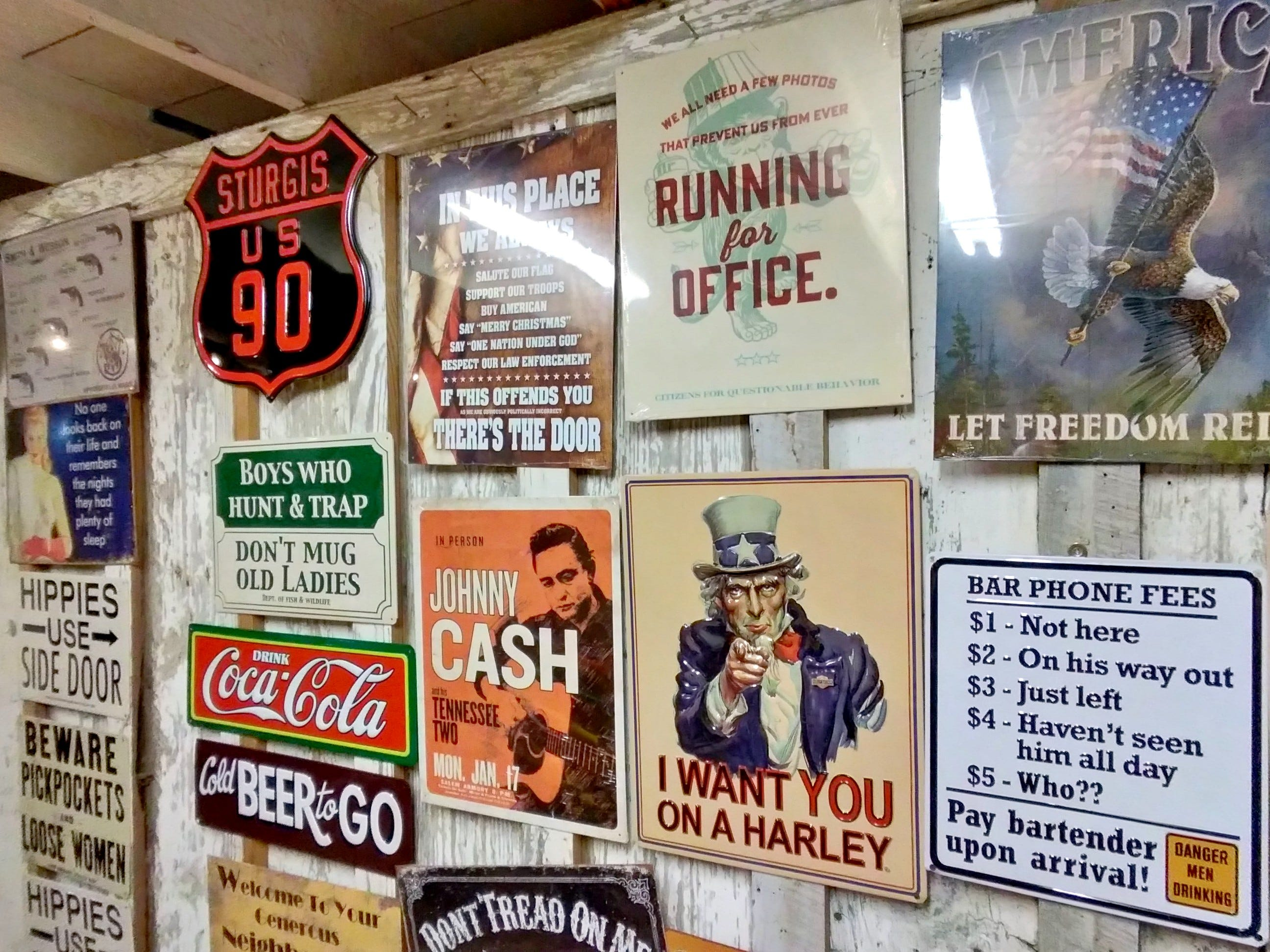 some tin signs on a wall in a small store