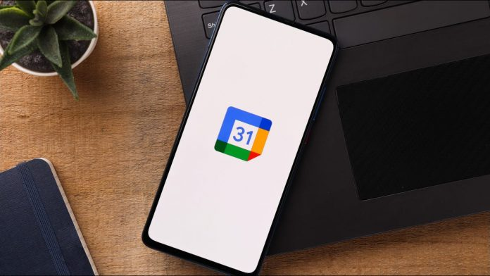 Smartphone on top of a laptop with the Google Calendar logo displayed