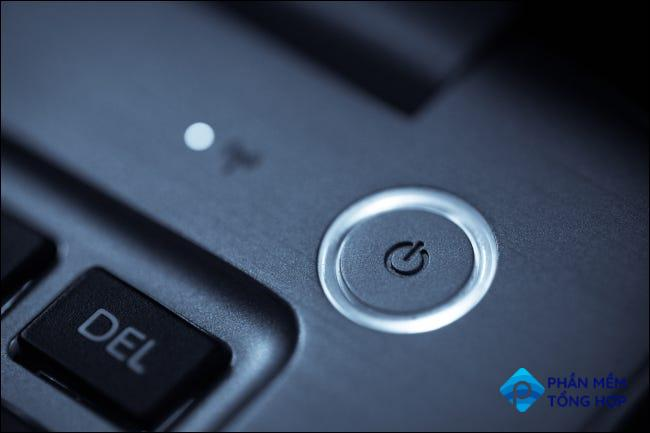 Closeup of a round power button at the corner of a laptop keyboard.